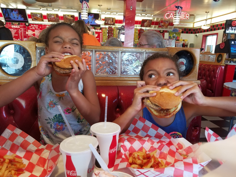 Look at these two cuties as they enjoy their hamburgers and ice cream.